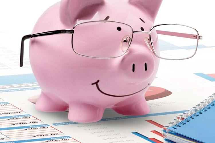 Pink piggy bank with reading glasses on top of financial paperwork next to a calculator