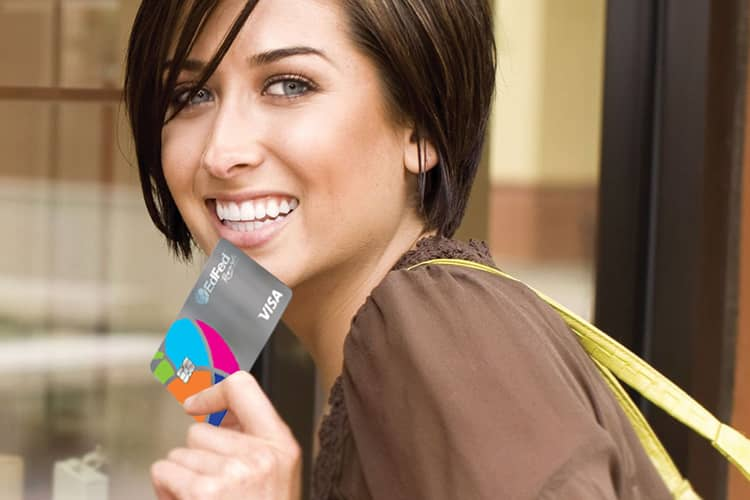 Woman smiling holding credit union credit card