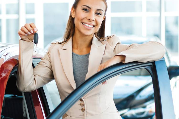 Smiling woman standing on drivers side of a red car holding a key.