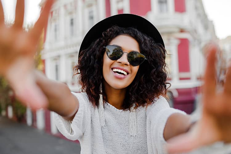 A young woman wearing sunglasses and a stylish hat smiling.