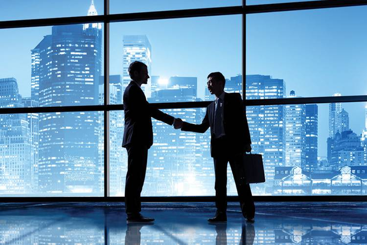 Business men shaking hands in front of a large window view of the city at night