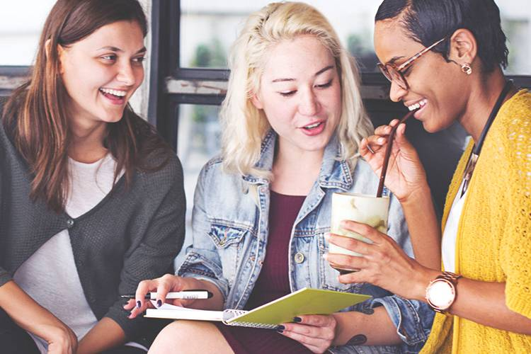 Three woman sitting together looking at a notebook and smiling