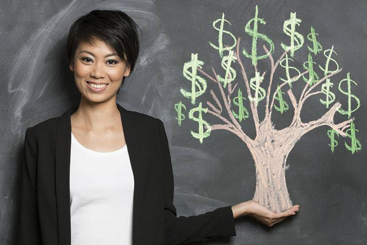 Woman standing against a blackboard with a money tree drawn with chalk.