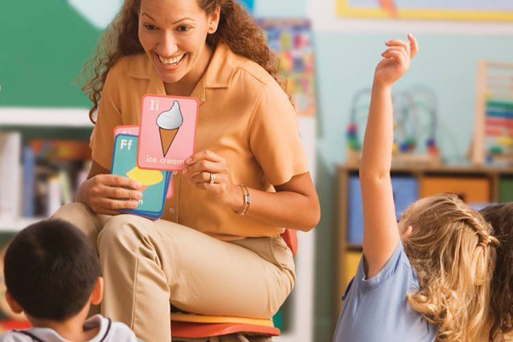 Teacher holding flash cards in front of students with raised hands
