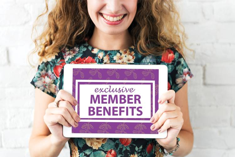 A woman smiling while holding a purple sign reading: Exclusive Member Benefits