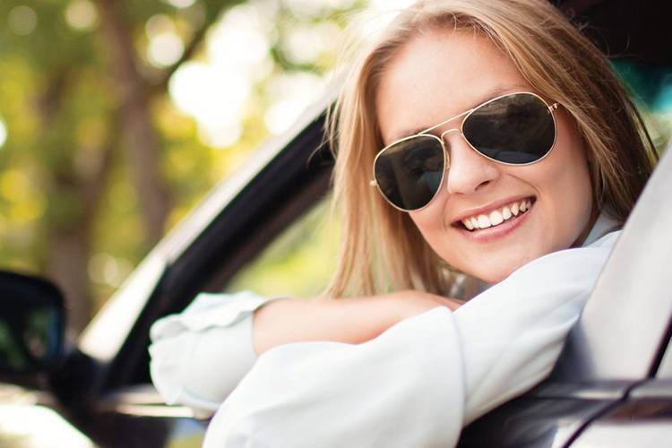 Woman smiling sitting in her car with sunglasses
